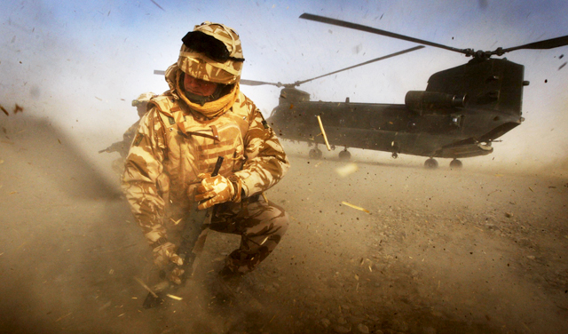 British soldier kneeling in front of Chinook helicopter